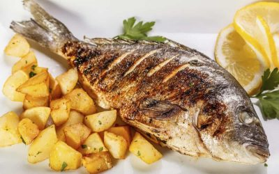 Sea bream fish with potato on white plate close-up